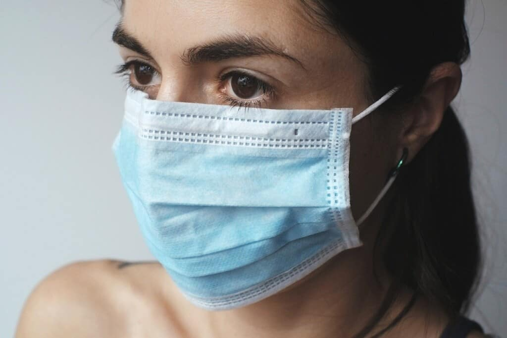A woman wearing a surgical mask.