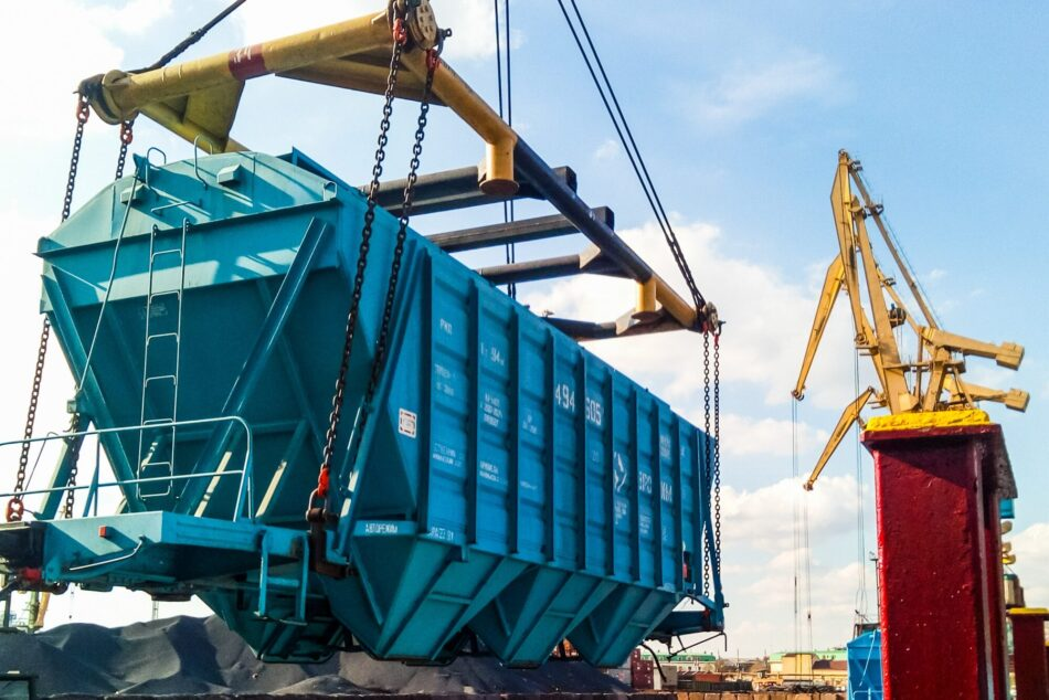 Raising the hopper car for unloading on a cargo ship. Lifting operations in the port.